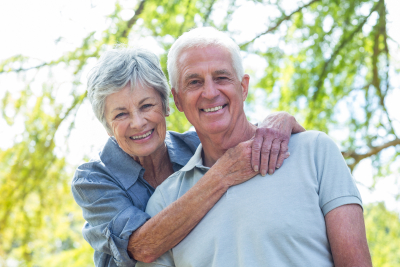 happy senior couple smiling in a park on a sunny day